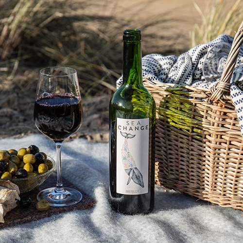 Bottle of Red Wine next to picnic basket