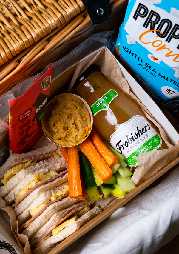 A picnic box with scones and cream with tea and sandwiches
